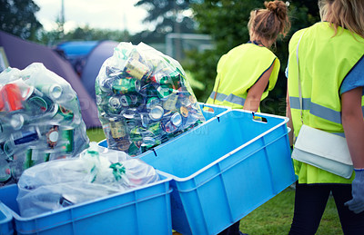 Buy stock photo Cropped shot of two young women picking up trash after a festival