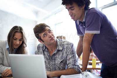 Buy stock photo Shot of a group of university students working on laptops in class