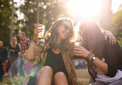 Buy stock photo Shot of two young friends enjoying a drink together at an outdoor festival