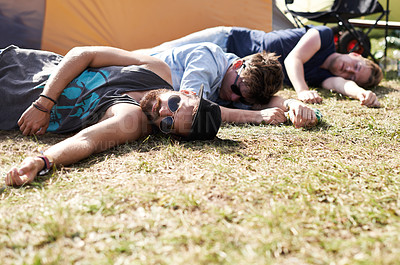 Buy stock photo Shot of three young men lying on the grass at an outdoor festival