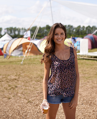 Buy stock photo Shot of a beautiful young woman holding a beer while standing at a campsite