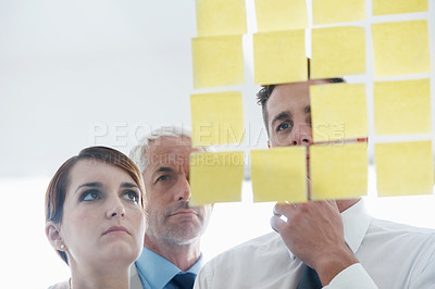 Buy stock photo Shot of coworkers arranging sticky notes on a glass wall during a brainstorming session