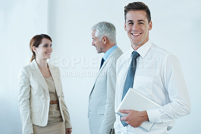 Buy stock photo Shot of a group of smiling business people looking at something on a laptop