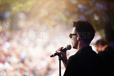Buy stock photo A singer performing on stage at an outdoor music festival