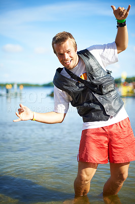 Buy stock photo Portrait of a young man knee deep in water at an outdoor festival