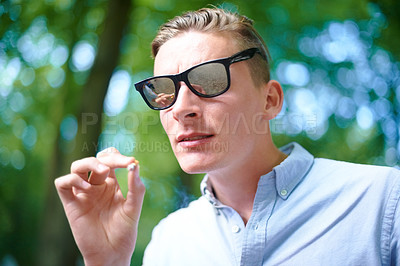 Buy stock photo Shot of a young man smoking a joint at an outdoor festival