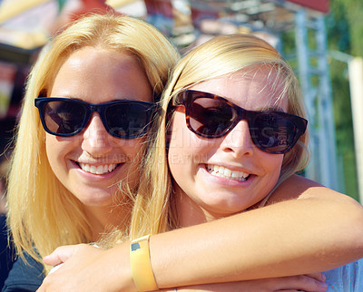 Buy stock photo Portrait of two female friends standing together at an outdoor festival
