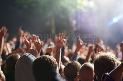 Buy stock photo Rear view shot of a crowd enjoying a live concert with their hands raised