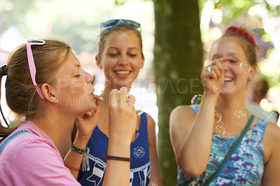 Buy stock photo Three young women blowing bubbles while socializing at a festival
