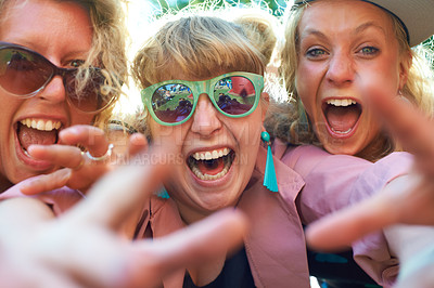 Buy stock photo Shot of a group of girlfriends enjoying themselves at an outdoor festival