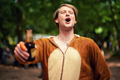 Buy stock photo Shot of a young man drinking outside while dressed in a bear suit