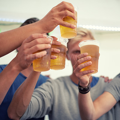 Buy stock photo Shot of a group of young men cheering with their beers