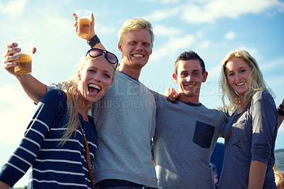 Buy stock photo Portrait of a group of young friends drinking beer outdoors