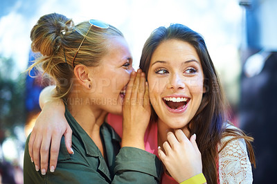 Buy stock photo A young woman whispering a secret in her friend's ear