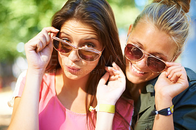 Buy stock photo Two young woman standing outside wearing sunglasses