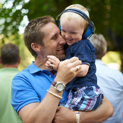 Buy stock photo Shot of a father hugging his little boy at an outdoor festival