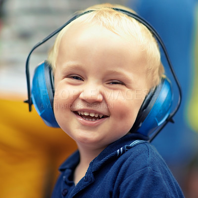 Buy stock photo Closeup portrait of a little boy laughing while wearing ear protectors at an outdoor music festival