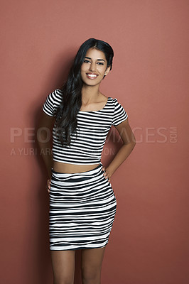 Buy stock photo Studio shot of a beautiful stylish young Indian woman against a red background