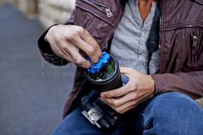 Buy stock photo A young man removing the lens from his camera
