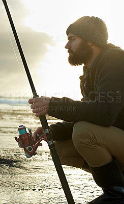 Buy stock photo Cropped shot of a bearded man fishing on the beach