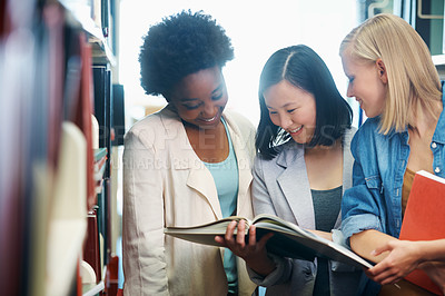 Buy stock photo Young people standing in the library and looking at a book together