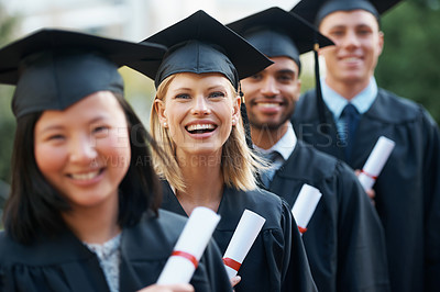 Buy stock photo Young college graduates holding their diplomas while standing in a row and smiling