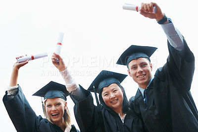 Buy stock photo A group of enthusiastic college graduates holding up their diplomas