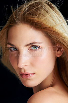 Buy stock photo A blonde woman posing in front of a black background while the wind blows through her hair