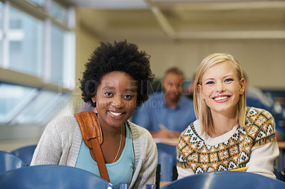 Buy stock photo Shot of two female college students working together in a lecture hall
