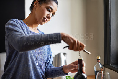 Buy stock photo A young woman opening a bottle of wine with dinner