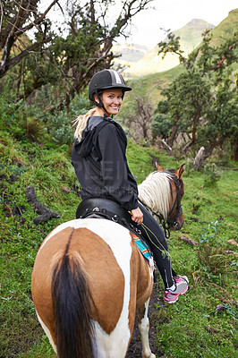 Buy stock photo An attractive young woman riding a horse on a mountain trail