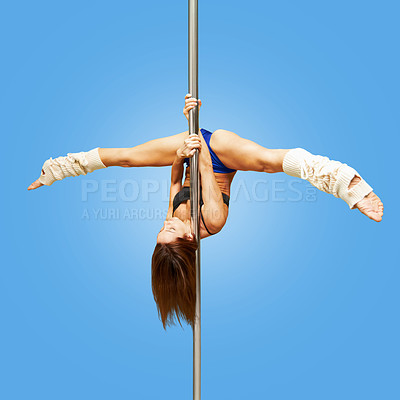 Buy stock photo Studio shot of a young woman hanging upside down on a pole against a blue background