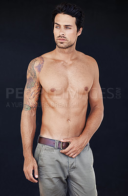 Buy stock photo Shot of handsome male with his shirt off with a dark background