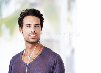 Buy stock photo Shot of a handsome man listening to music and looking deep in thought