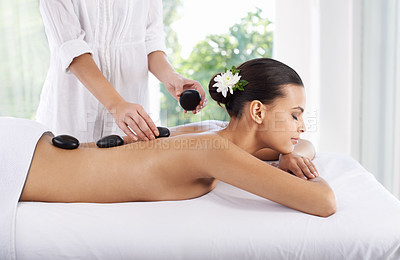 Buy stock photo A young woman receiving a hot stone massage