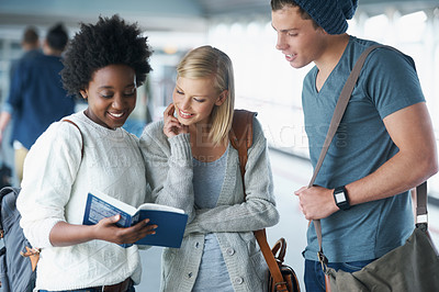 Buy stock photo A group of college students looking at a book together