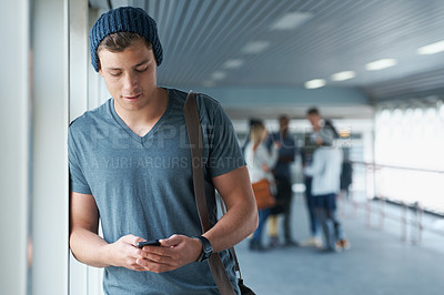 Buy stock photo Shot of a handsome young college student holding a cellphone with friends in the background
