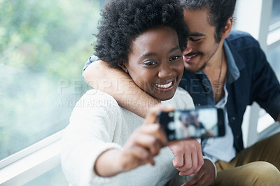 Buy stock photo A young woman taking a photo of herself and her boyfriend with a smartphone