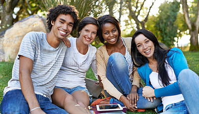 Buy stock photo Shot of a diverse group of college students sitting outside using digital tablet