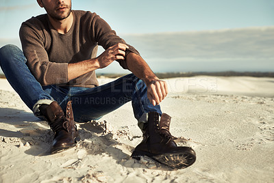 Buy stock photo A man wearing jeans and boots sitting on the beach