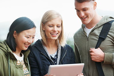 Buy stock photo Shot of a group of university students looking at something on a digital tablet