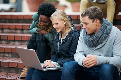 Buy stock photo Shot of a group of university students looking at something on a laptop
