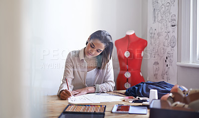 Buy stock photo A young fashion designer making sketches in her office