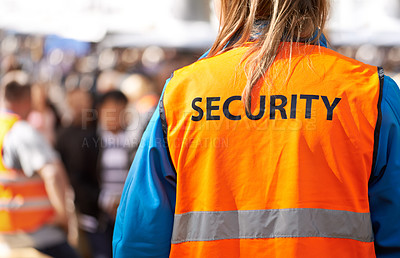 Buy stock photo Rearview shot of a security officer standing outdoors with a crowd in the background