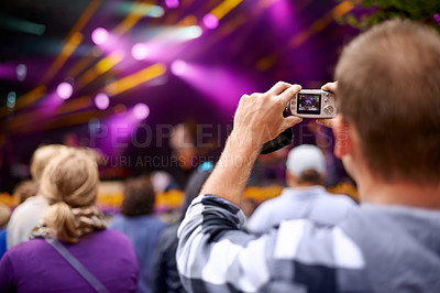 Buy stock photo Rearview shot of a man in the crowd holding a camera to photograph a concert