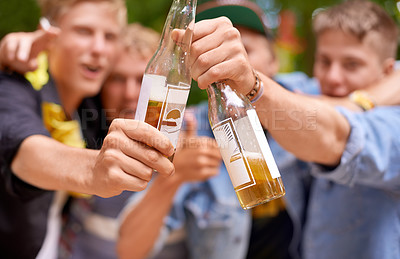 Buy stock photo Cropped shot a group of young men toasting with beer bottles