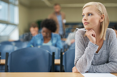 Buy stock photo A pretty blonde student writing exam in a lecture hall