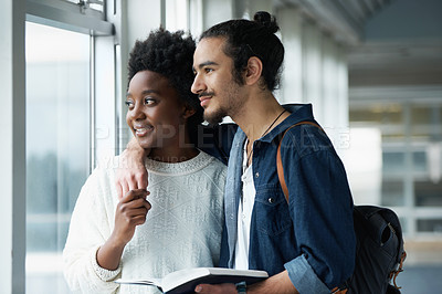 Buy stock photo A Couple in University holding hands and holding a textbook while looking out the window