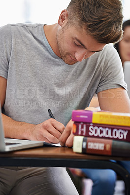 Buy stock photo A handsome young student sitting at a desk with her textbooks