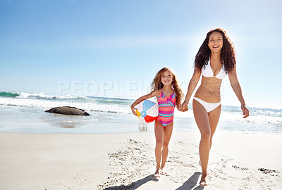 Buy stock photo Shot of a young mother and her daughter at the beach